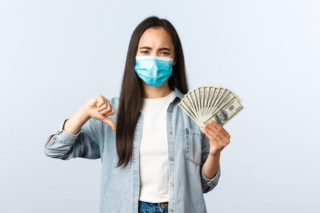 사회적 거리를 두는 생활 방식, covid-19 전염병 비즈니스 및 고용 개념. 화나고 실망한 아시아 소녀는 엄지손가락을 아래로 내리고 더러운 돈을 보여주고, 싫어하는 사람은 뇌물을 받았습니다.