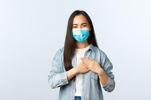 社会的距離を置くライフスタイル、covid-19パンデミックの日常生活とレジャーの概念。喜んで幸せなアジアの女の子が賞賛され、感動と感謝を感じ、心に触れ、医療マスクで笑っている