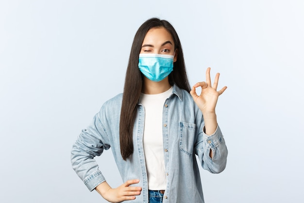 Social distancing lifestyle, covid-19 pandemic everyday life and leisure concept. pleased calm and confident asian girl in medical mask, wink and show okay sign in approval, guarantee quality.