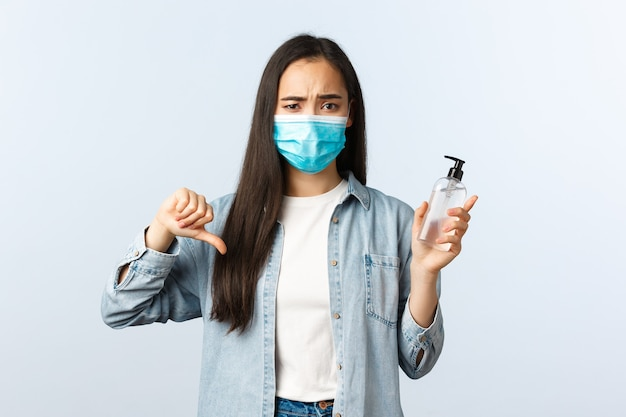 사회적 거리를 두는 생활 방식, covid-19 전염병 예방 바이러스 개념. 의료용 마스크를 쓴 실망한 아시아 여성은 나쁜 제품을 승인하지 않고 판단하고, 끔찍한 손 소독제를 보여주고, 엄지손가락을 아래로 내립니다.