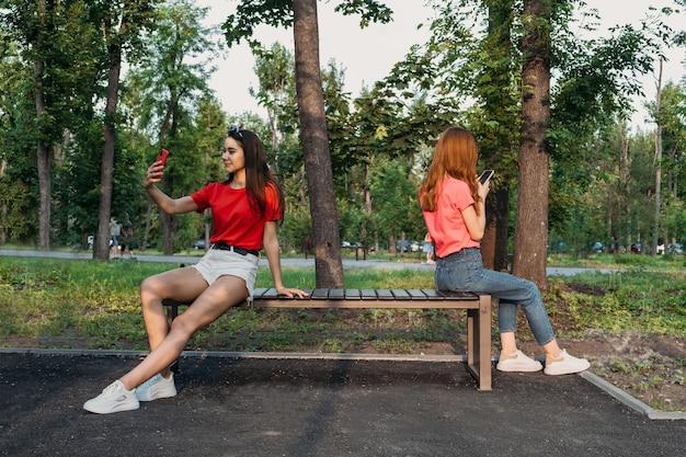 사회적 거리두기, 새로운 정상 개념. 벤치에 앉아 휴대 전화와 두 여자 여자 친구
