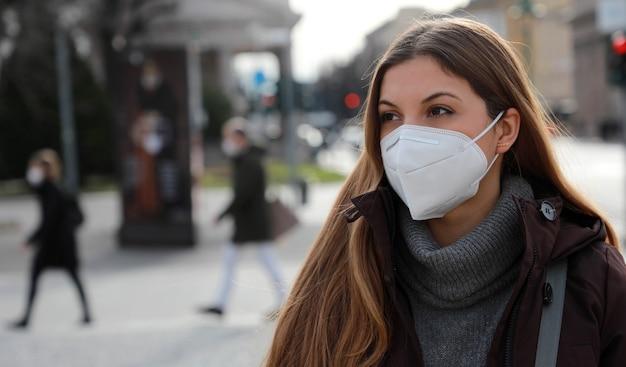 社会的距離は尊重されます。屋外の冬の服でffp2kn95フェイスマスクを身に着けている若い女性の肖像画。