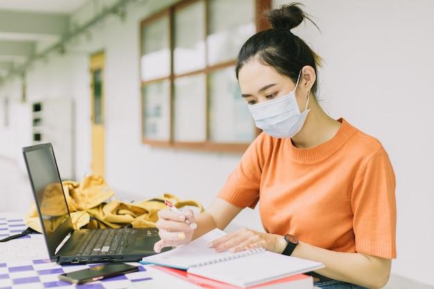Концепция обучения самоизоляции социального дистанцирования, девушка-подросток из азиатского университета учится наедине с маской для лица в кампусе