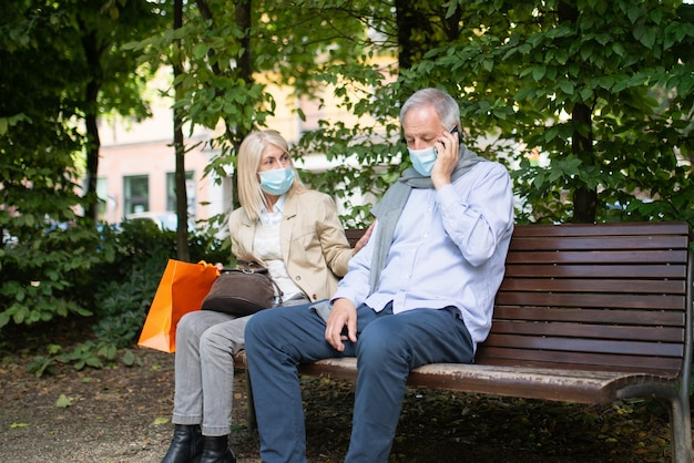 Social distancing and separation concept, coronavirus prevention while sitting on a bench in a park concept