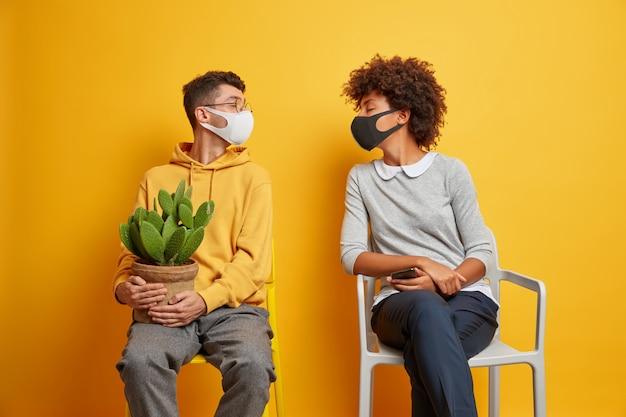 집에 머무르는 사회적 거리감과 코로나 바이러스 전염병 개념. 혼혈 젊은 여자와 남자는 격리 된 의자에 격리 포즈를 취하는 동안 보호 마스크를 착용합니다.