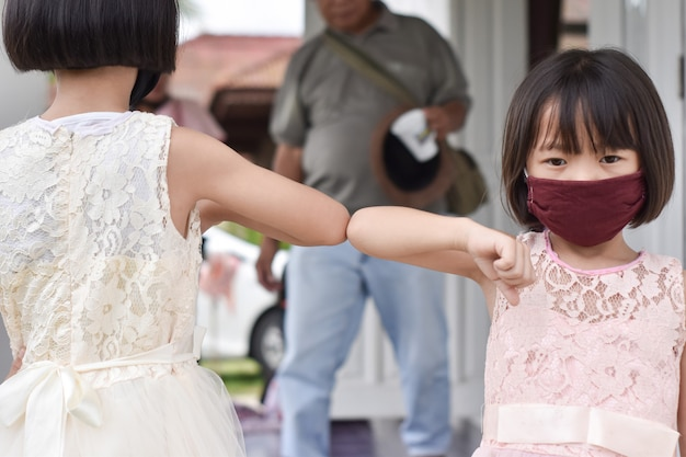 Social distancing. two children bump elbows new novel greeting. friends demonstrating to avoid the spread of coronavirus.