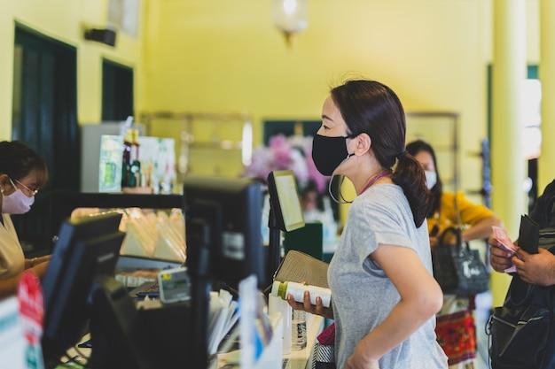 防護マスクを身に着けている社会的距離のある女性がカフェのカウンターでドリングを注文します。