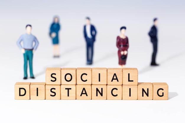 Social distancing in wooden blocks and little figurines