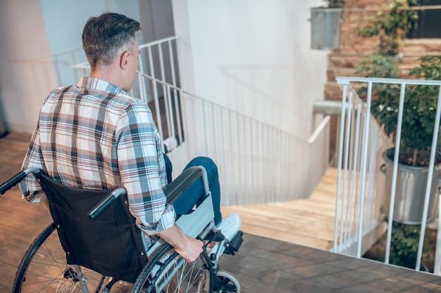 사회 불안. 실내 계단 근처에서 우유부단하게 서 있는 휠체어에 격자 무늬 셔츠를 입은 남자의 뒤에서 보기
