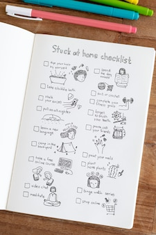 Social isolation doodle style checklist in a notebook