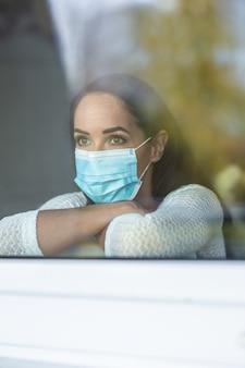 격리 중 사회적 고립은 집에서 창문 뒤에 앉아 있는 여성의 우울한 기분에 영향을 줍니다.