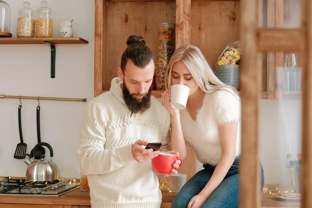 소셜 미디어 중독. 부부는 부엌에서 커피를 마시고, 스마트 폰을 사용하여 뉴스 피드와 게시물을 확인합니다.