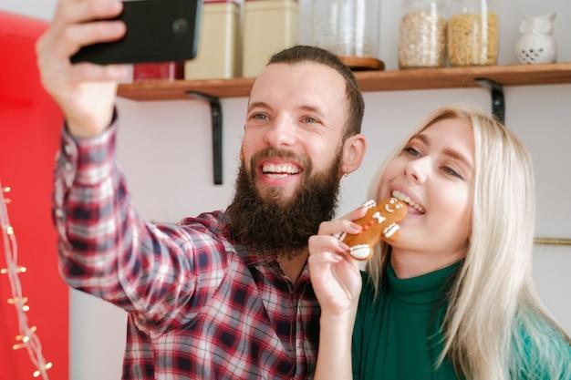 Зависимость от социальных сетей. веселая пара с помощью смартфона, чтобы сделать селфи с пряничным человечком на кухне.