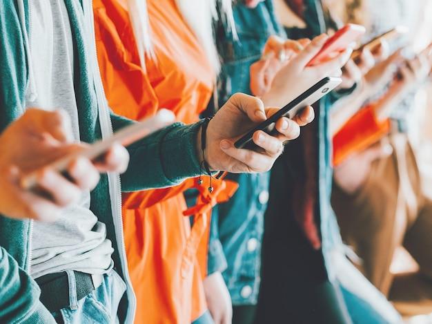Зависимость от социальных сетей. ряд людей со смартфонами. образ жизни миллениалов. технология досуга.