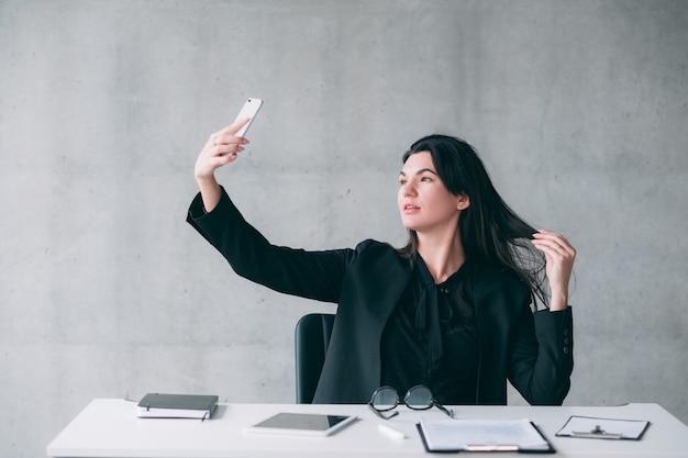 Зависимость от социальных сетей. успешная деловая женщина, делающая селфи на своем офисном столе, позирует. скопируйте пространство.