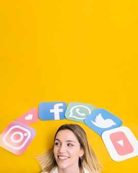 Social media application icons over the happy woman's head on yellow backdrop