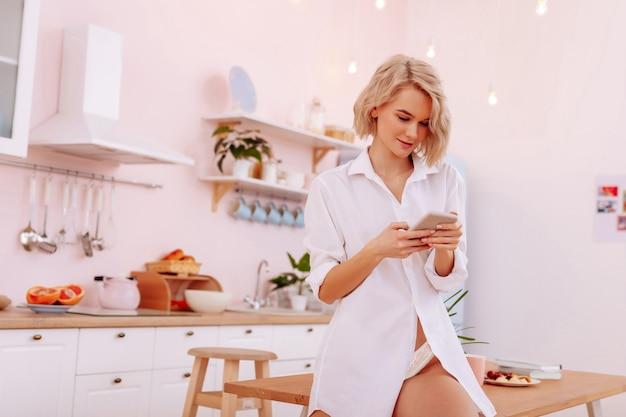 소셜 미디어. 아침에 소셜 미디어를 확인하는 금발 머리의 젊은 밀레니얼 여성