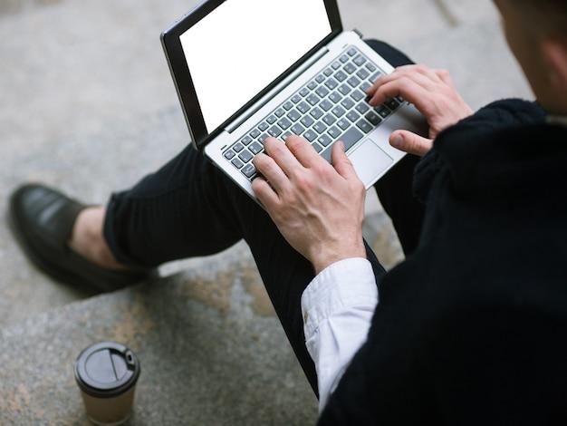 ソーシャルメディアコミュニケーション。男性のための技術。リモートワーク、屋外でチャットしている認識できないビジネスマンの上面図、空の白い画面のモックアップとラップトップ