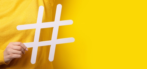 Social media concept, closeup of human hand holding and showing large big white hashtag sign