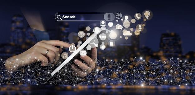 ソーシャルメディアの概念。通信ネットワーク。デジタルホログラムソーシャルメディアアイコンと手タッチ白いタブレットは、都市の暗いぼやけた背景に署名します。ソーシャルメディアまたはソーシャルネットワークの通知。