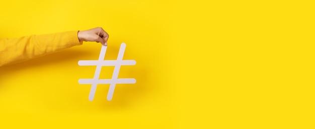 Концепция социальных сетей, рука держит большой белый знак хэштега