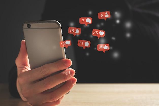 オンライン活動を伴うソーシャルメディアの概念。人はスマートフォンを使用します。