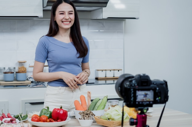 Social media concepts a happy woman standing in the kitchen using a camera and recording video online happy asian woman vlogger broadcast live online video teaching to cook in the kitchen at home.