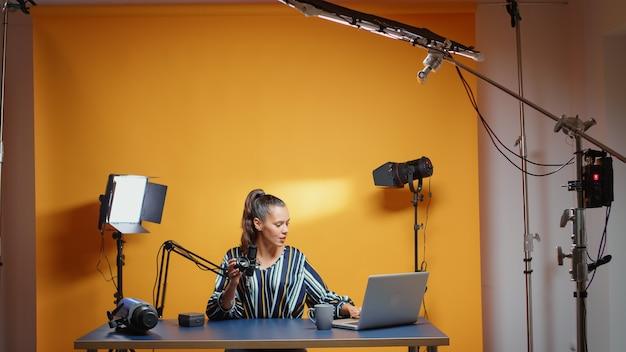 전문 레코드 스튜디오 세트에서 새로운 렌즈를 검토하는 소셜 미디어 전문가. 콘텐츠 제작자 뉴 미디어 스타 인플루언서 온라인 인터넷 웹 쇼를 위한 비디오 사진 장비 이야기