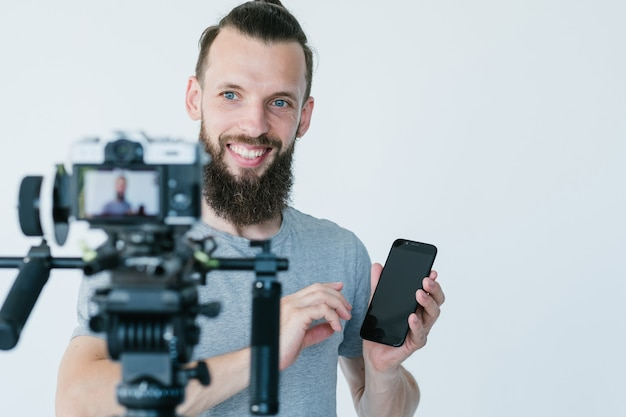 職場でのソーシャルメディアインフルエンサー。ブロガーがコマーシャルまたは独立したレビューを撮影しています。カメラの前で携帯電話を持っている男。趣味は儲かるビジネスに変わりました。