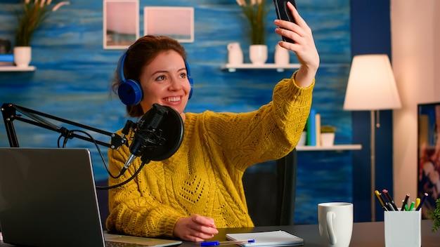청중을 위해 셀카 녹화 팟 캐스트 시리즈를 촬영하기 위해 전화를 사용하는 소셜 미디어 인플 루 언서