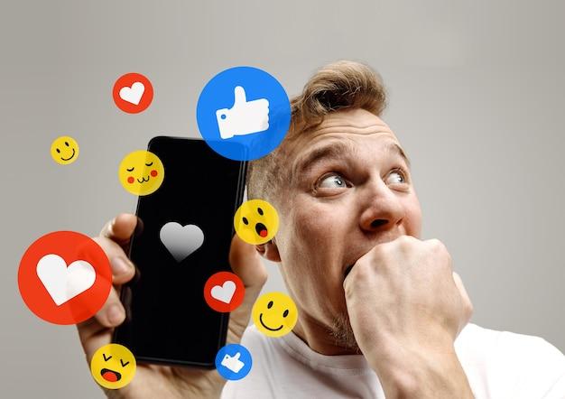 携帯電話でのソーシャルメディアの相互作用。インターネットデジタルマーケティング、チャット、コメント、いいね。スマートフォンの画面上の笑顔とアイコン、灰色のスタジオの背景に若い男が保持しています。