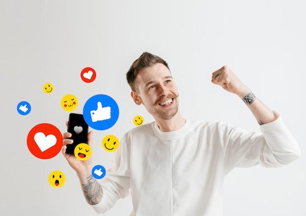 携帯電話でのソーシャルメディアの相互作用。インターネットデジタルマーケティング、チャット、コメント、いいね。スマートフォンの画面上の笑顔とアイコン、白いスタジオの背景に若い男が持っている。