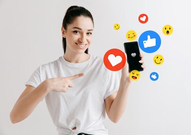 携帯電話でのソーシャルメディアの相互作用。インターネットデジタルマーケティング、チャット、コメント、いいね。スマートフォンの画面上の笑顔とアイコン、白いスタジオの背景に若い女性が持っている。