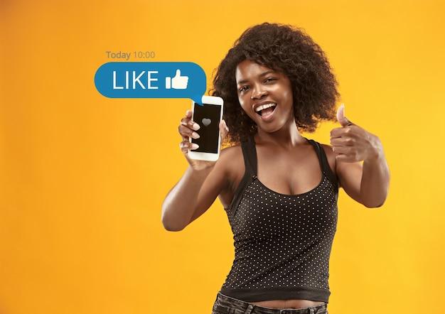 携帯電話でのソーシャルメディアの相互作用。インターネットデジタルマーケティング、チャット、コメント、いいね。スマートフォンの画面上の笑顔とアイコン、黄色のスタジオの背景に若い女性が保持しています。