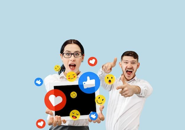 携帯電話でのソーシャルメディアの相互作用。インターネットデジタルマーケティング、チャット、コメント、いいね。タブレット画面の上の笑顔とアイコン、青いスタジオの背景に若いカップルが持っている。