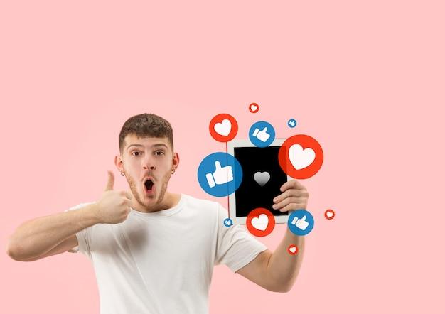 携帯電話でのソーシャルメディアの相互作用。インターネットデジタルマーケティング、チャット、コメント、いいね。タブレット画面の上の笑顔とアイコン、コーラルスタジオの背景に若い男が持っている。