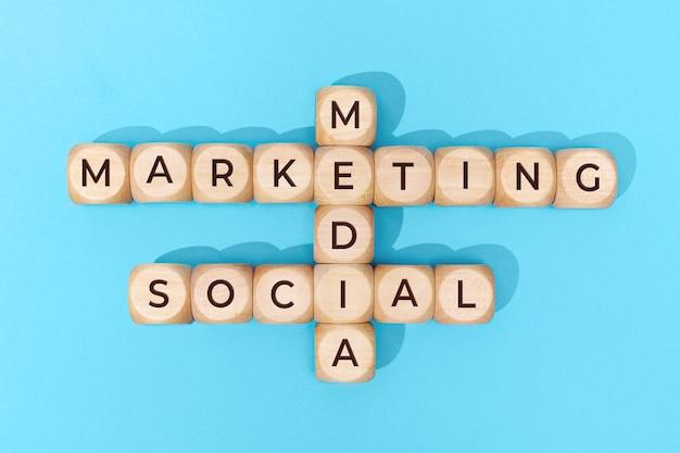 Маркетинговые слова в социальных сетях на деревянных блоках на синем фоне. вид сверху