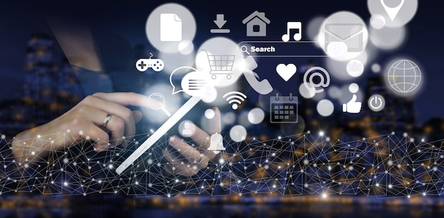 ソーシャルメディアまたはソーシャルネットワークの通知。デジタルホログラムソーシャルメディアアイコンと手タッチ白いタブレットは、都市の暗いぼやけた背景に署名します。ソーシャルメディアの概念。通信ネットワーク。