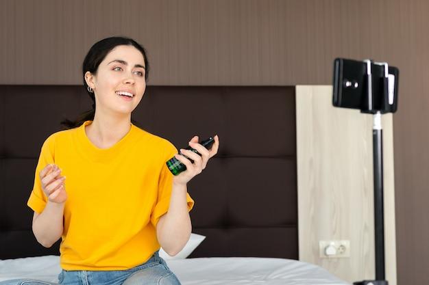 Социальные медиа. портрет красивой улыбающейся женщины-влогера, транслирующей видео в реальном времени на смартфоне и тестирующей косметику.