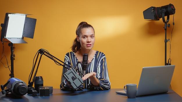 그녀의 스튜디오에서 전문적인 v lock 배터리 검토를 하는 소셜 미디어 스타. 소셜 미디어에서 콘텐츠 제작자 뉴미디어 스타 인플루언서가 전문 비디오 촬영 장비를 검토합니다.