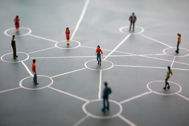 Концепция социальной сети: подключенные миниатюрные люди на зеленой доске