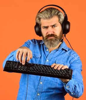ソーシャルネットワーク。インターネットから音楽をダウンロードする。あごひげを生やした男のヘッドフォンとキーボード。プロのゲーマーコンピューターゲームをプレイします。オンラインチャット。オンラインビデオゲーム。サイバーチャンピオンシップ。アジャイルビジネス。