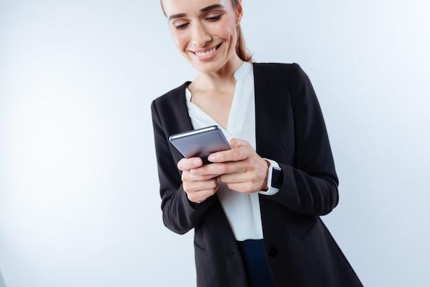 Социальная сеть. веселая милая молодая женщина держит свой мобильный телефон и набирает сообщение, улыбаясь