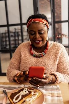 소셜 네트워킹. 메시지를 읽는 동안 웃 고 기쁘게 아프리카 계 미국인 여자