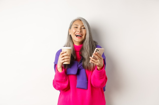 Rete sociale. felice donna anziana asiatica che beve caffè e tiene in mano uno smartphone, ride di macchina fotografica, in piedi su sfondo bianco