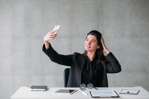 Одержимость социальными сетями. нарцистическая деловая женщина, делающая селфи на своем офисном столе, позирует.