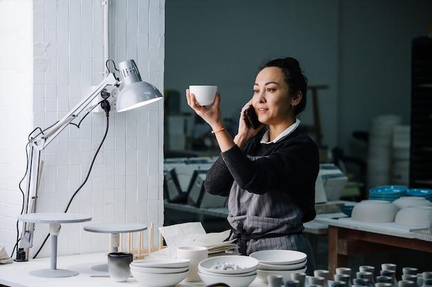 새로 생성 된 빈 식기 및 도구가있는 테이블의 램프 아래에서 컵을 검사하는 사회 여성