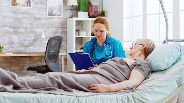 병원 침대에 누워 있는 노인 장애인 여성과 상담하는 사회 복지사. 간병인은 클립보드를 사용하여 연금 수급자 메모를 작성합니다.