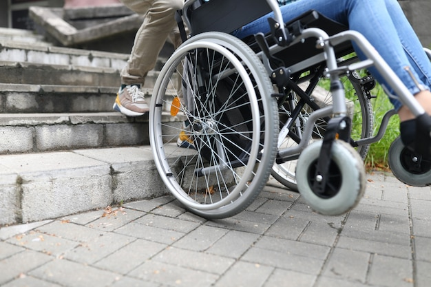 Social worker helps disabled person in wheelchair climb stairs