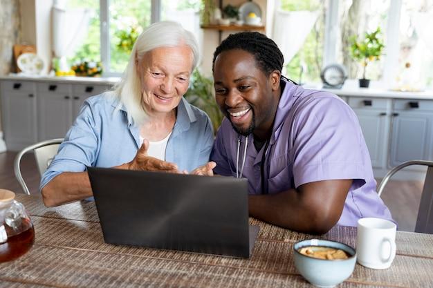 Социальный работник, глядя на ноутбук с пожилой женщиной